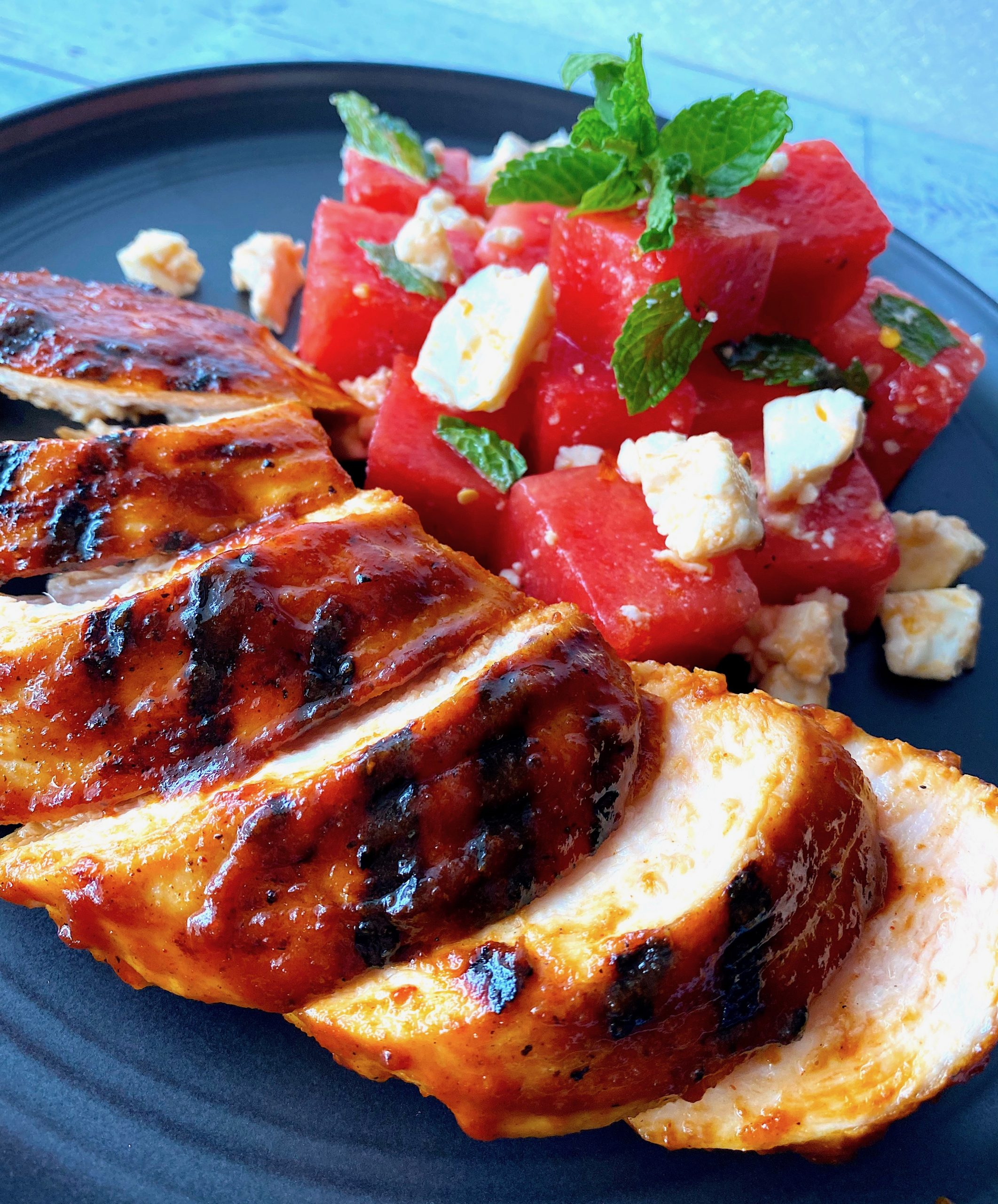 chicken breast with bbw sauce and a watermelon salad