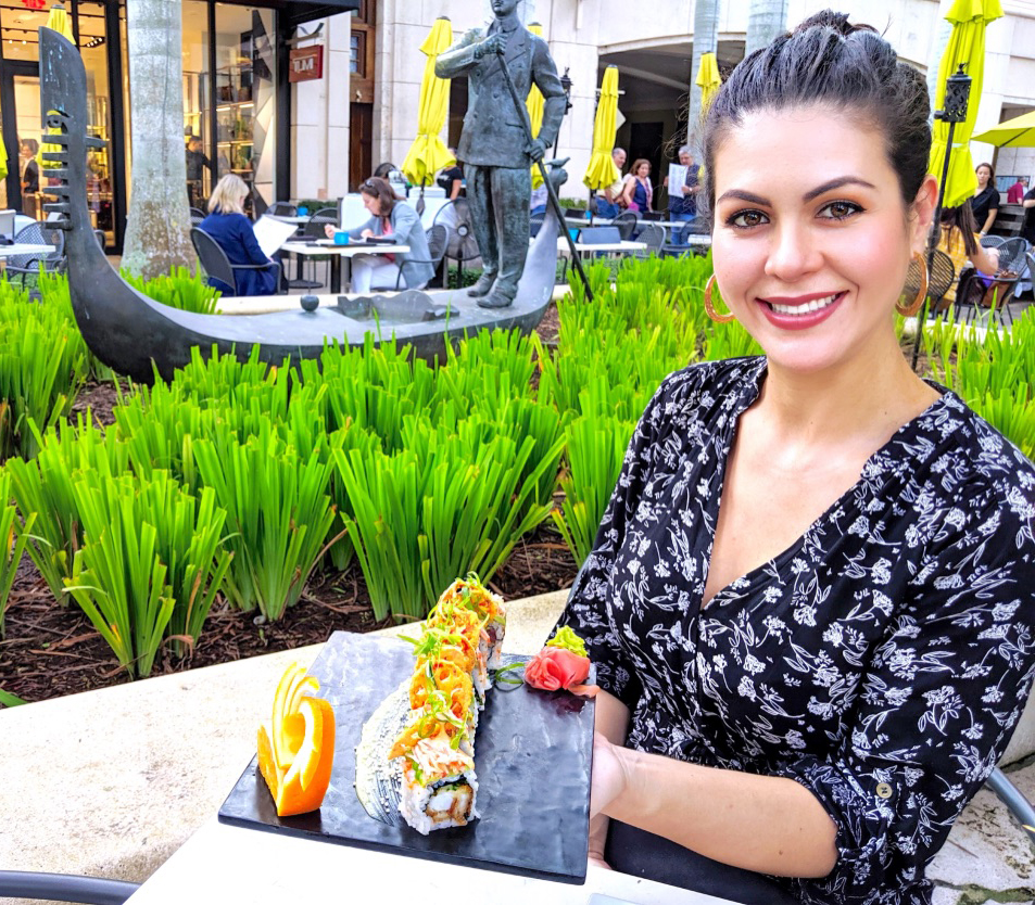 Yuly - smiling lady sitting in a restaurant patio hiding a plate of sushi